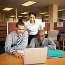 front view of businesswoman standing and two businessmen sitting working together on laptop