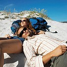 young couple with backpack relaxing on beach