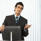 portrait of a businessman standing behind a podium giving a speech