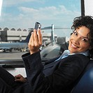 businesswoman at airport terminal resting in chair and using  pda with view of airplane through window