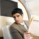 close up of businessman distracted while reading newspaper in first class airplane