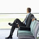 side view of businessman sitting in airport lounge