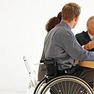 Business executives having a meeting around a table and one of them sitting in a wheelchair