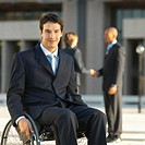 Businessman sitting in a wheelchair and two business executives shaking hands in the background