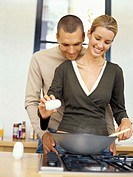 young woman cooking food with a young man embracing her from behind in the kitchen