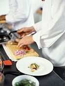 mid section view of two chefs cooking food in the kitchen
