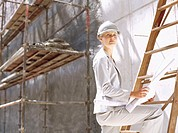 female architect holding a blueprint and standing on a ladder