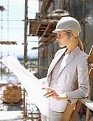 female architect holding a blueprint and wearing a hands-free device