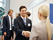 businessman shaking hands with a businesswoman at an exhibition