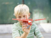 close-up of a boy playing with a toy airplane