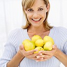 Portrait of woman holding lemons in her hands