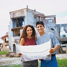 portrait of a couple looking at blueprint and house under construction in background