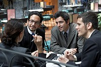 Four business executives having a meeting in a restaurant