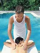 Man massaging woman lying by swimming pool