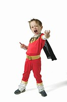 Boy (3-5) wearing superhero costume, thrusting hand out