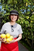 Senior woman holding lemons beside lemon tree, smiling, portrait