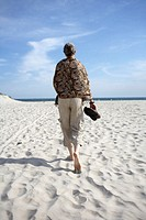 Mature woman walking on beach, rear view