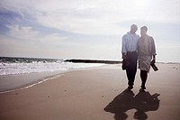 Couple walking along beach, smiling
