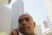 Businessman talking on mobile phone outdoors, low angle view