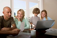 Parents looking at paperwork, children (5-8) using laptop