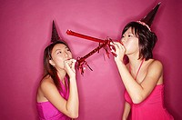 Young women wearing party hats, blowing noisemakers