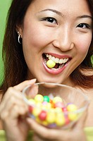 Woman biting candy and holding candy bowl