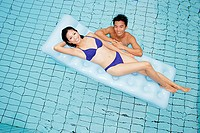 Woman in blue bikini lying on pool raft, man in water next to her