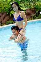 Couple in swimming pool, woman on mans shoulders, smiling at camera