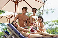 Young adults in swimwear, toasting with drinks