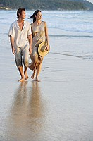 Couple walking on beach, looking away