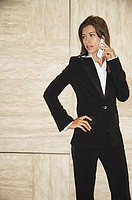 Businesswoman using mobile phone, looking away, hand on hip