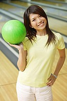 Woman at bowling alley with green bowling ball