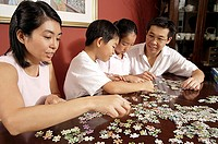 Family of four working on jigsaw puzzle