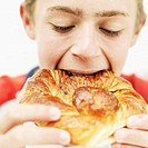 close-up of a teenage boy eating a danish pastry