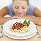 young woman looking at a plate of spaghetti bolognaise
