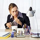 Businesswoman sitting at her desk and opening a bottle of vodka