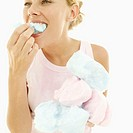Young woman eating candy-floss