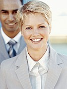 portrait of a businesswoman smiling with a businessman standing behind her