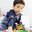 boy building a toy truck with building blocks on the bed