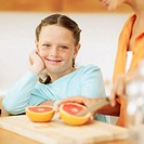 Close-up of a young girl (8-10) watching her mother cut a grapefruit