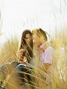 teenage couple sitting in a field