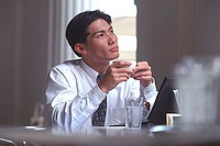 Male executive holding coffee cup in cafe, thoughtful expression