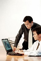 Two male executives working on laptop computer.