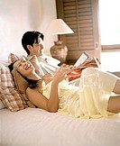 Woman and man in bed holding magazines, laughing