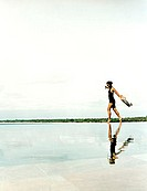 Woman running on water´s edge with reflection.