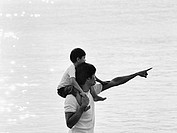 Father and son at beach, son on father´s shoulders