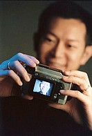 Man holding digital camera, black background ( high grain)
