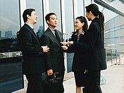 Executives meeting outside building.