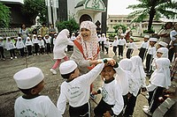Indonesia, Riau Islands, Tanjung Pinang, Muslim teacher playing with students.