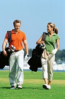 young couple carrying golf bags